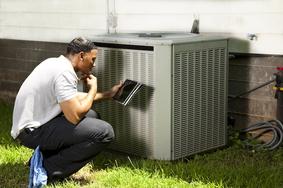 Technician performing AC maintenance