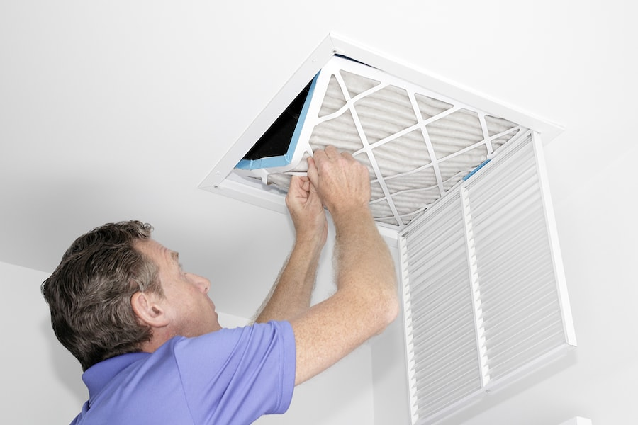 Technician installing new filter to help air conditioning system eliminate mold in home.