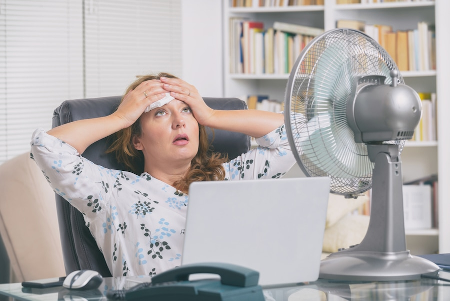 woman trying to stay cool due to not following the 4 signs she needs a new ac unit