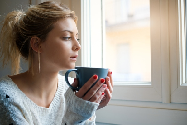 Woman sitting by window with hot drink trying to decide if HVAC preventative maintenance is worth it