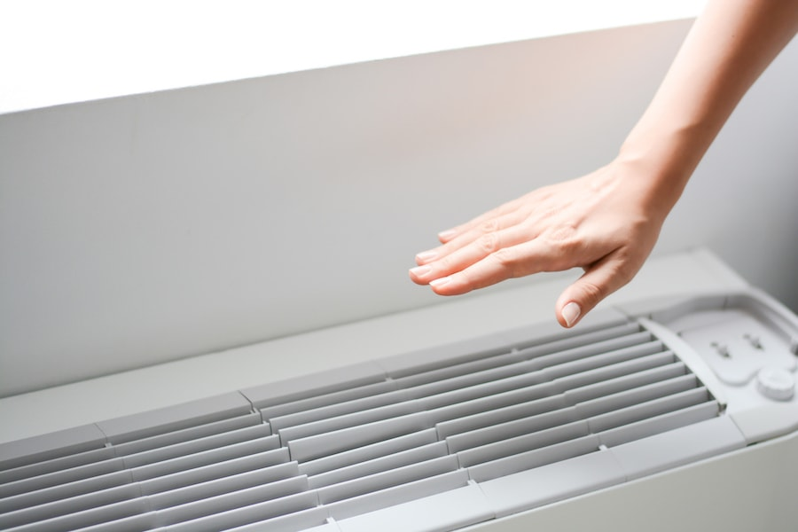 Homeowner checking the air flow or temperature after following their AC maintenance checklist.