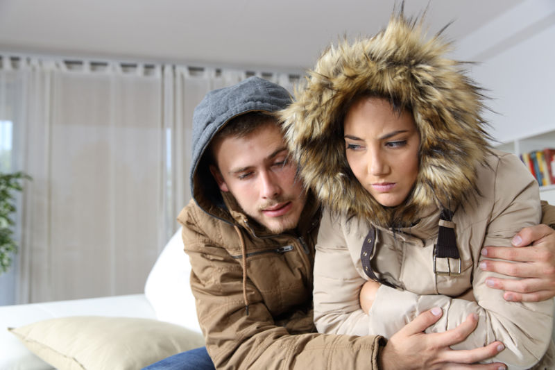 cold couple sitting at home wondering why their furnace is blowing cold air.
